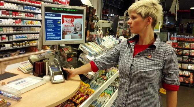 So geht's: Unsere Kollegin Anne Böckel, Mitarbeiterin an der Westfalen Tankstelle Weseler Str. 383 in Münster, zeigt, wie das kontaktlose Zahlen mit Smartphone funktioniert.