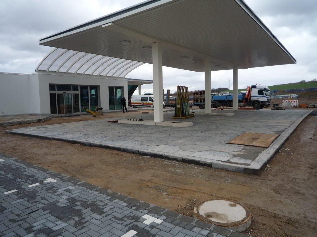 Hier entstehen drei verschiedene Bodenbeläge: die flüssigkeitsdichte Fahrbahn, eine Bitumenfläche für die Fahrbahn, sowie Pflaster für die PKW-Parkplätze.